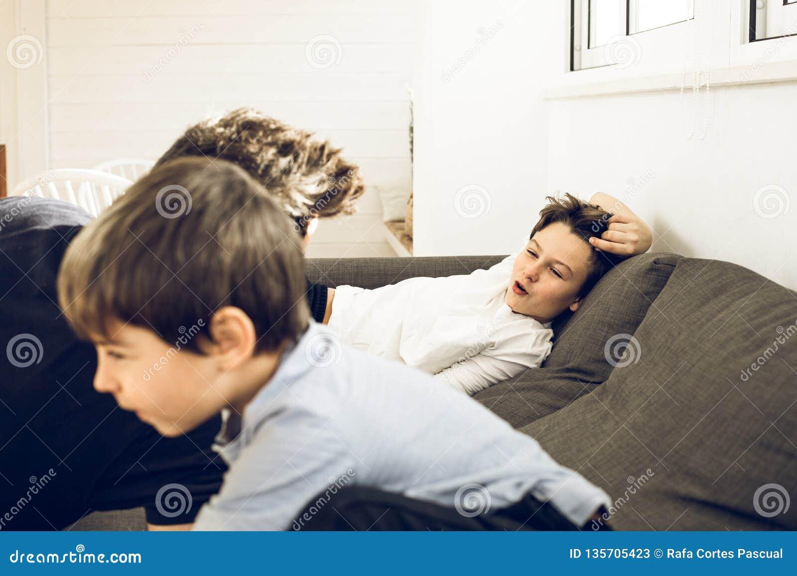 Vater, der zu Hause mit seinen Kindern auf der Couch spielt