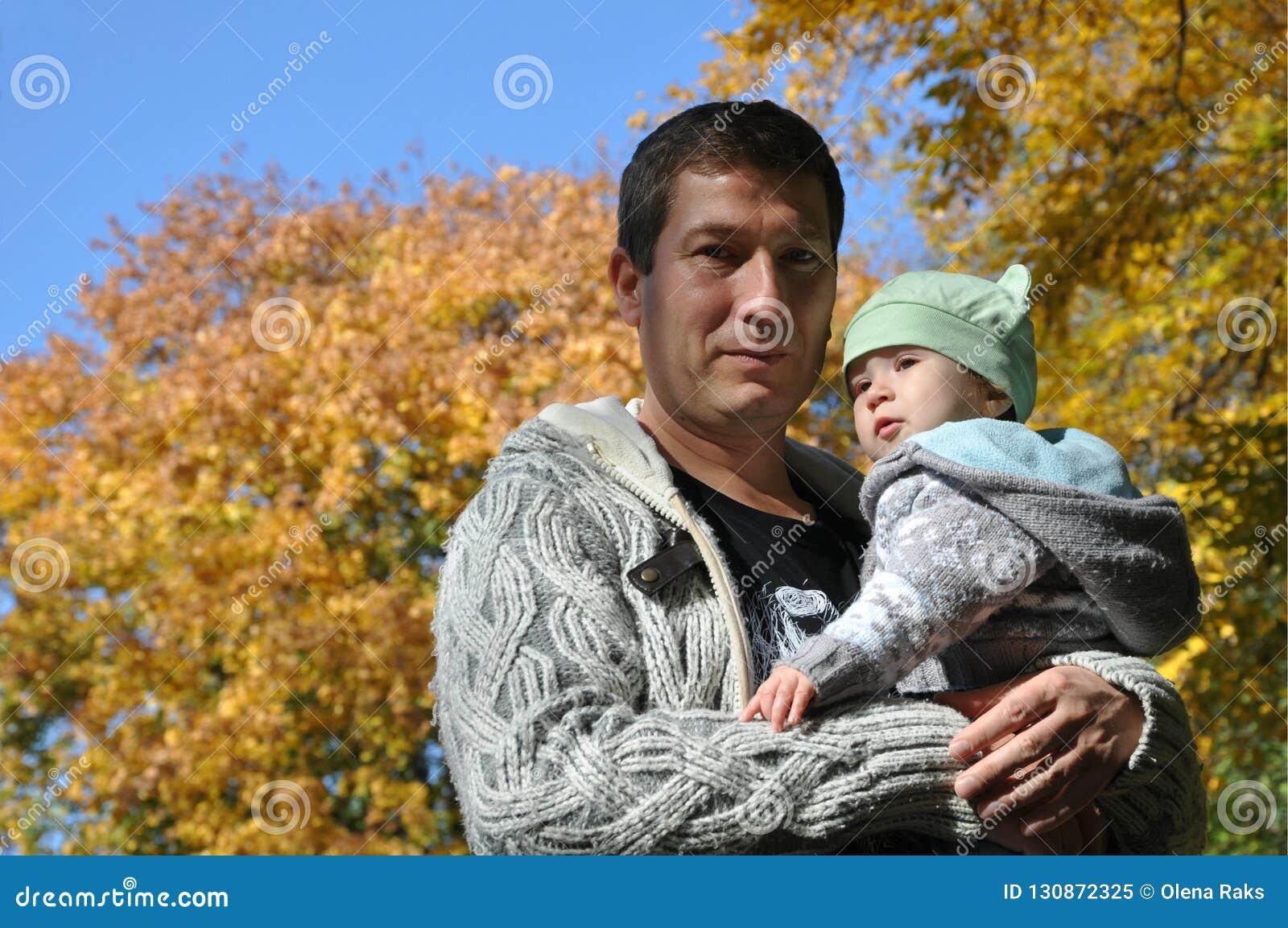 Vater und Baby auf dem herbstlichen Hintergrund