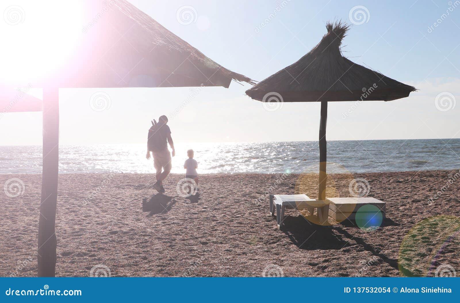 Vater und Junge, die auf dem Strand zur Sonnenuntergangzeit, Konzept der freundlichen Familie spielen