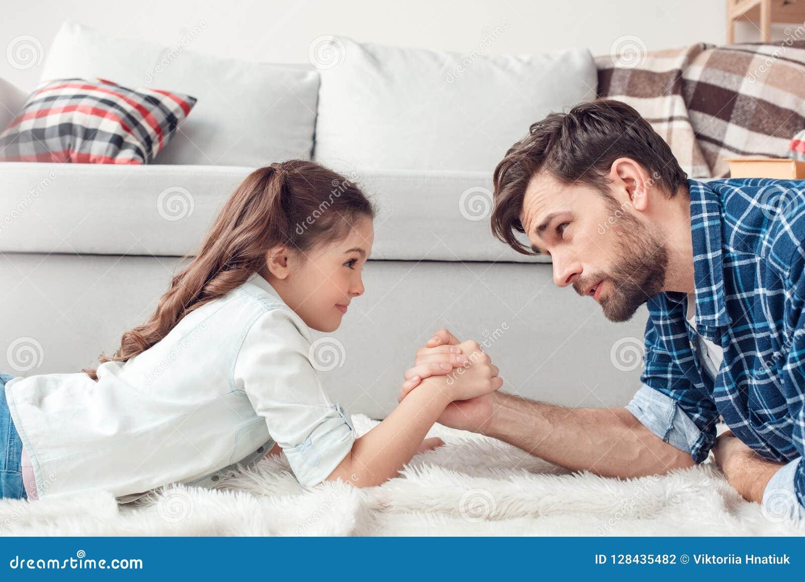 Vater und kleine Tochter zu Hause, die auf dem Boden lässt das Armdrückenwettbewerbslächeln aufregen liegt