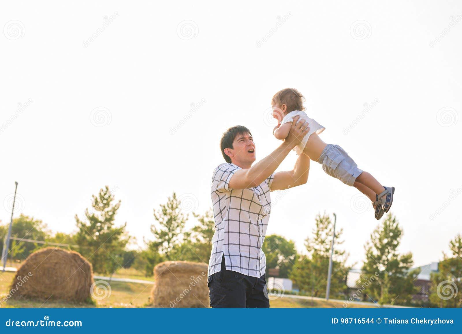 Vater und Sohn, die auf dem Feld zur Tageszeit spielen Leute, die Spaß draußen haben Konzept der freundlichen Familie
