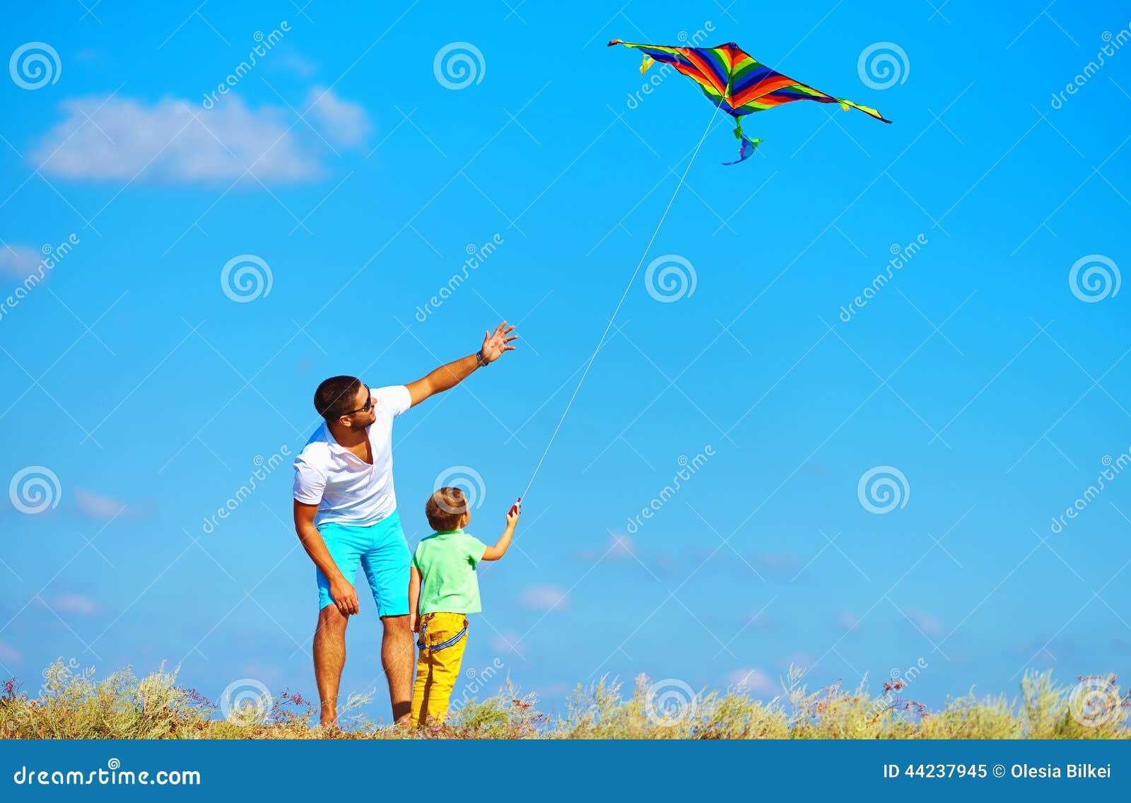 Vater und Sohn, die den Spaß, zusammen spielend mit Drachen hat