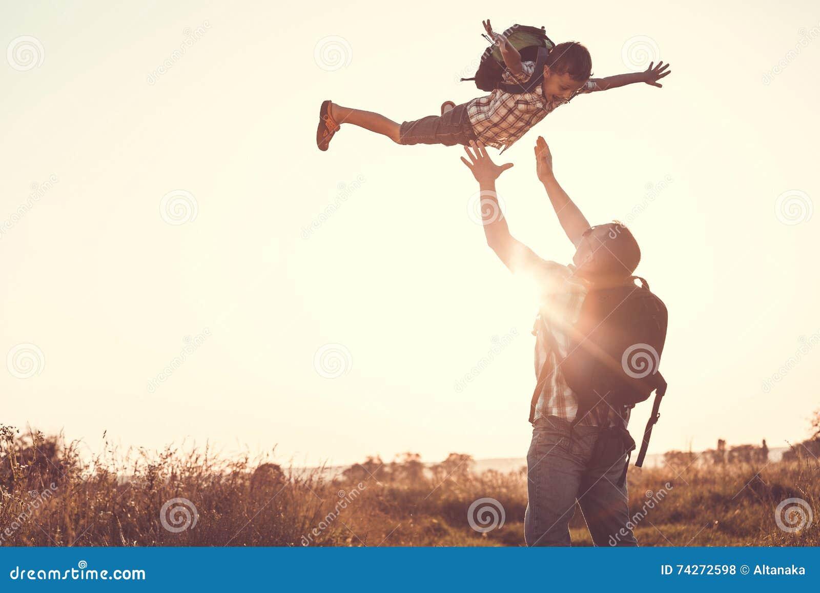 Vater und Sohn, die im Park zur Sonnenuntergangzeit spielen