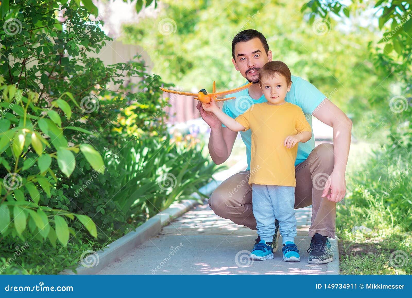Vater und Sohn, die zusammen draußen am Sommertag spielen: Vati und Kind starten Spielzeugflugzeug Neuer Anfang, elterliches Hilf