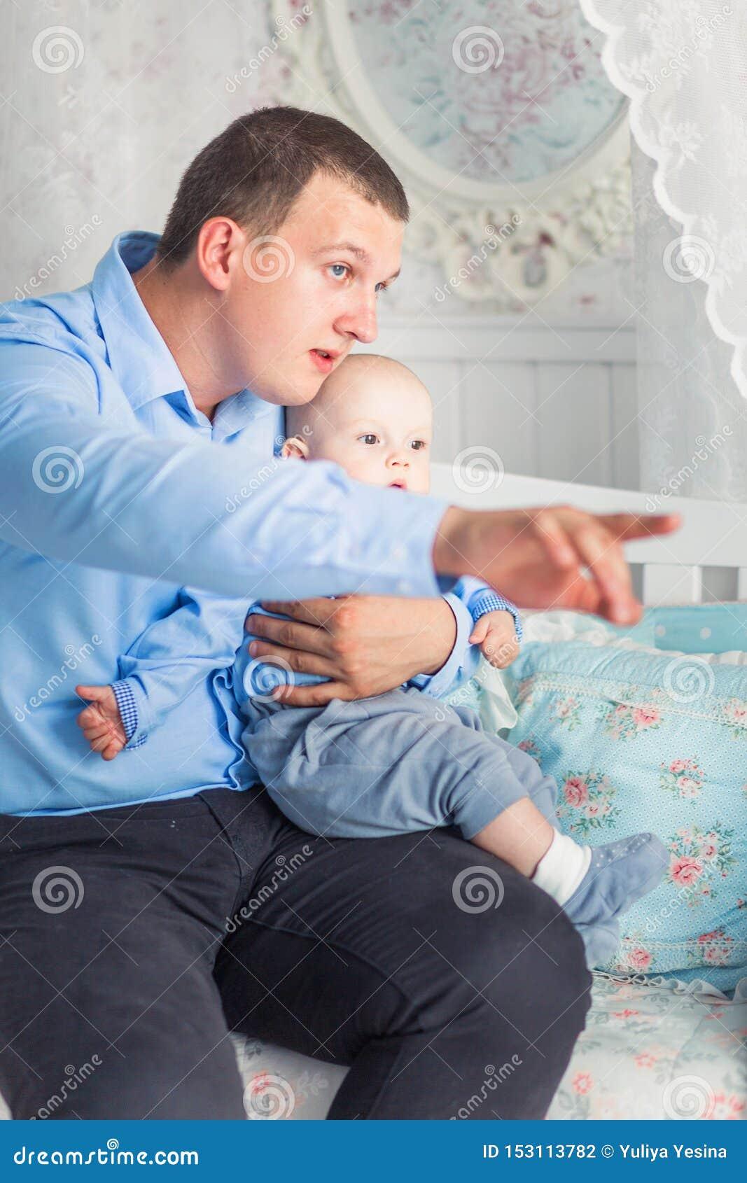 Vater und Sohn sitzen im Kinderzimmer Vati zeigt seinem Sohn etwas