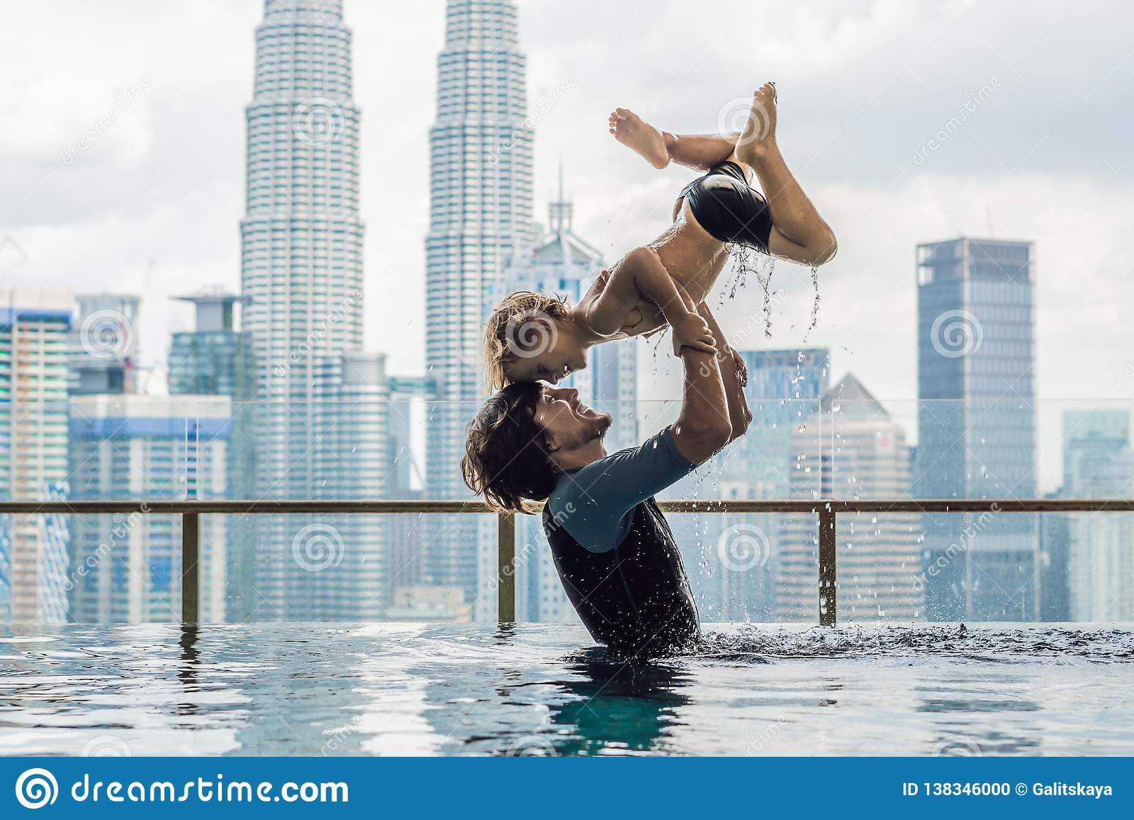 Vater und Sohn Swimmingpool im im Freien mit Stadtansicht in blauen Himmel