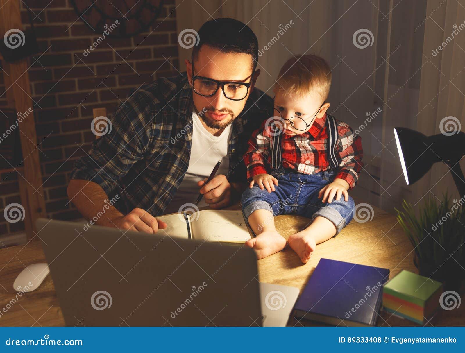 Vater- und Sohnbaby arbeiten zu Hause am Computer in der Dunkelheit