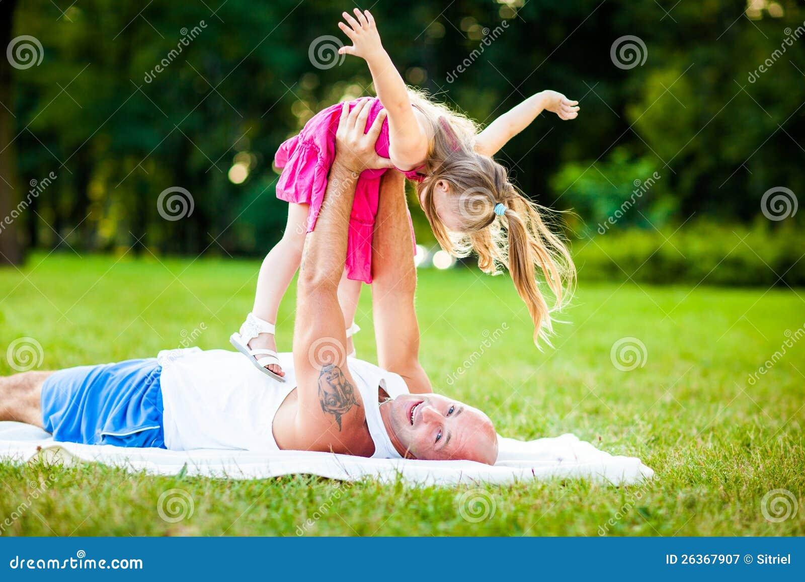 Vater und Tochter, die Spaß in einem Park haben