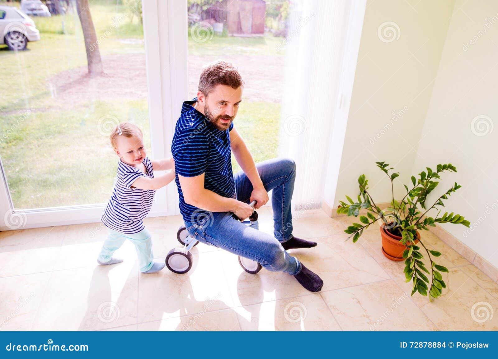 Vater und Tochter, die zusammen, ein Fahrrad zuhause reiten spielt