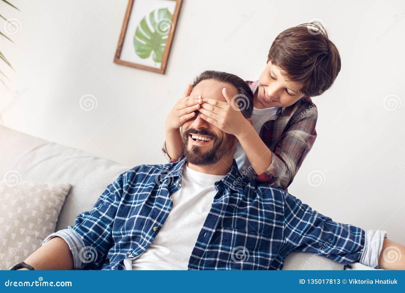 Vater Und Wenig Junge Des Sohns Zu Hause, Welche Die Augen