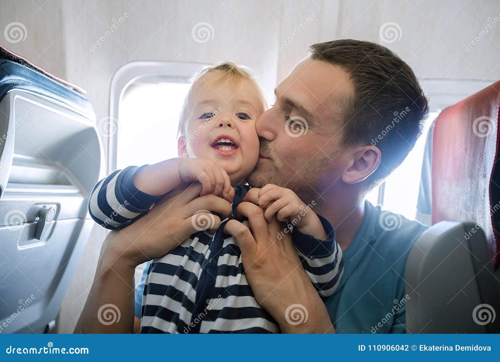 Vati küsst seinen Innenraum des Sohns im Flugzeug