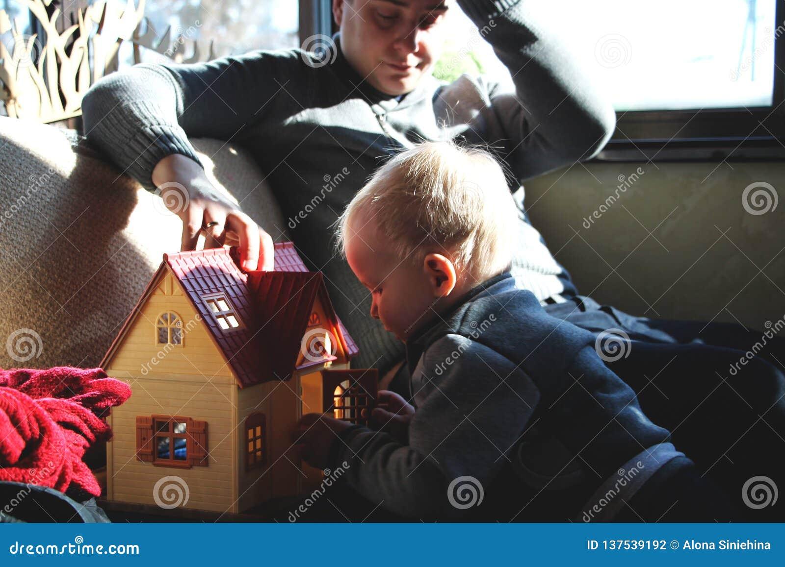 Vati und Sohn spielen im Puppenhaus