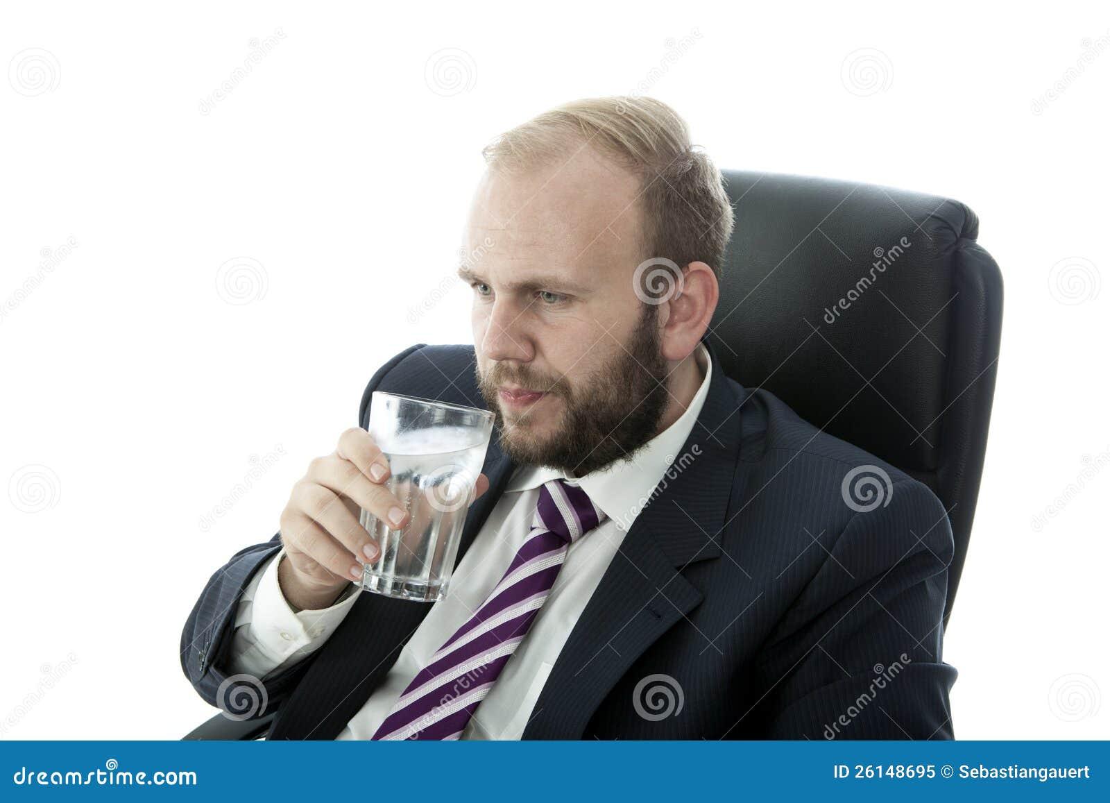 Vatten för drink för skäggaffärsman glass medan arbete
