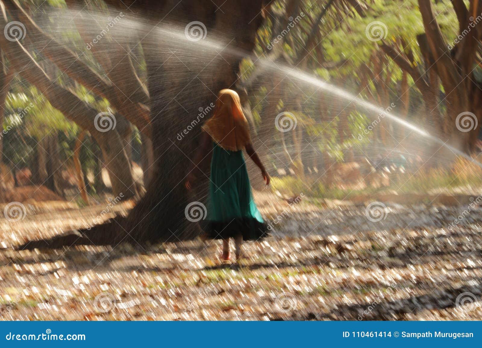 Vatten för flickadansbestänkande med trädbakgrund i gröngöling-förbud parkerar