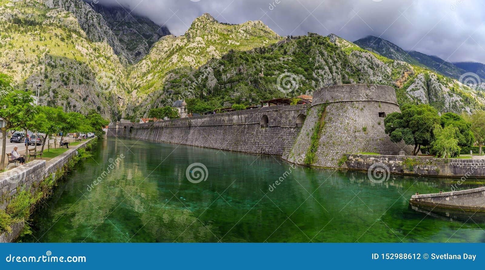Vatten för smaragdgräsplan av den Kotor fjärden eller Boka Kotorska och den forntida väggen av Kotor den tidigare Venetian fästni