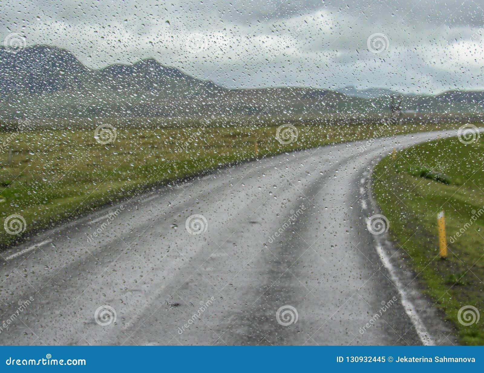 Vatten tappar på bilfönster efter regnet med den ensamma vägen mellan berg på en bakgrund, södra Island, Europa