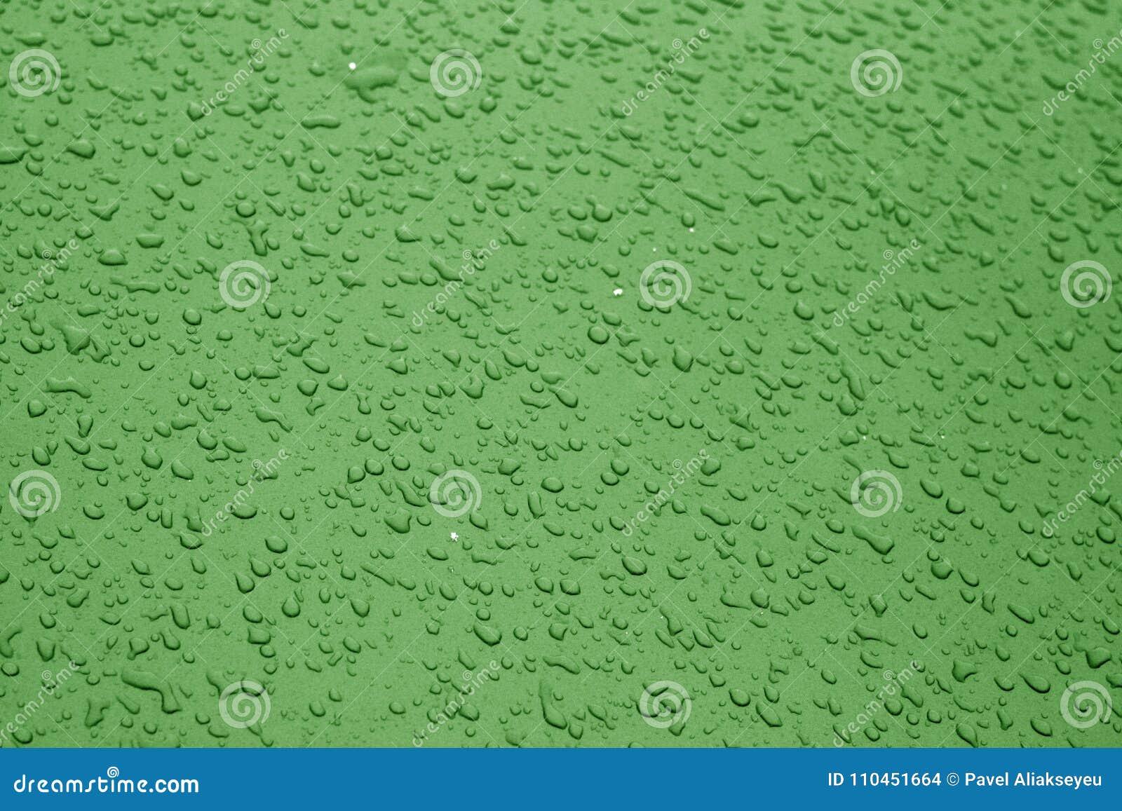 Vattendroppar på yttersida för blåttfärgmetall med suddighetseffekt i gree