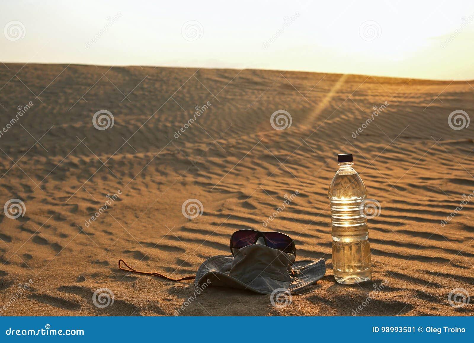 Vattenflaska, Hatt Och Solglasögon Som Ligger På Sanden I