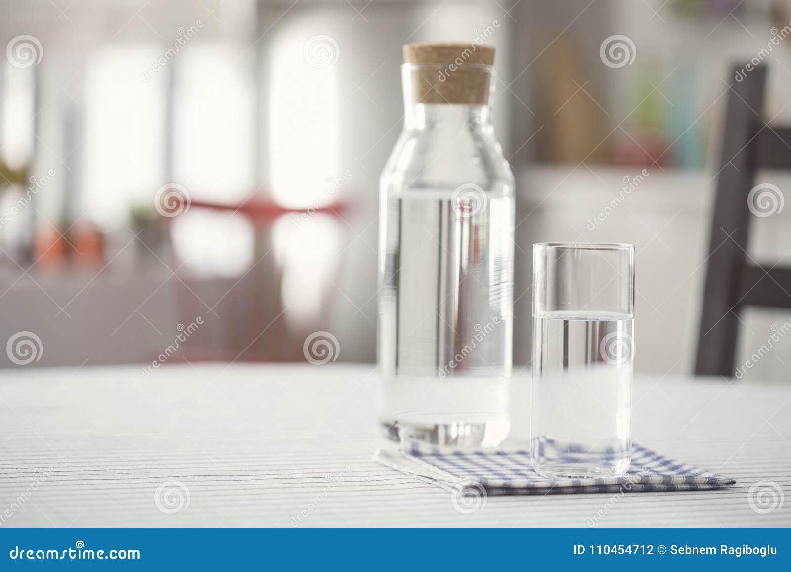 Vattenflaska och exponeringsglas av vatten på köksbordet