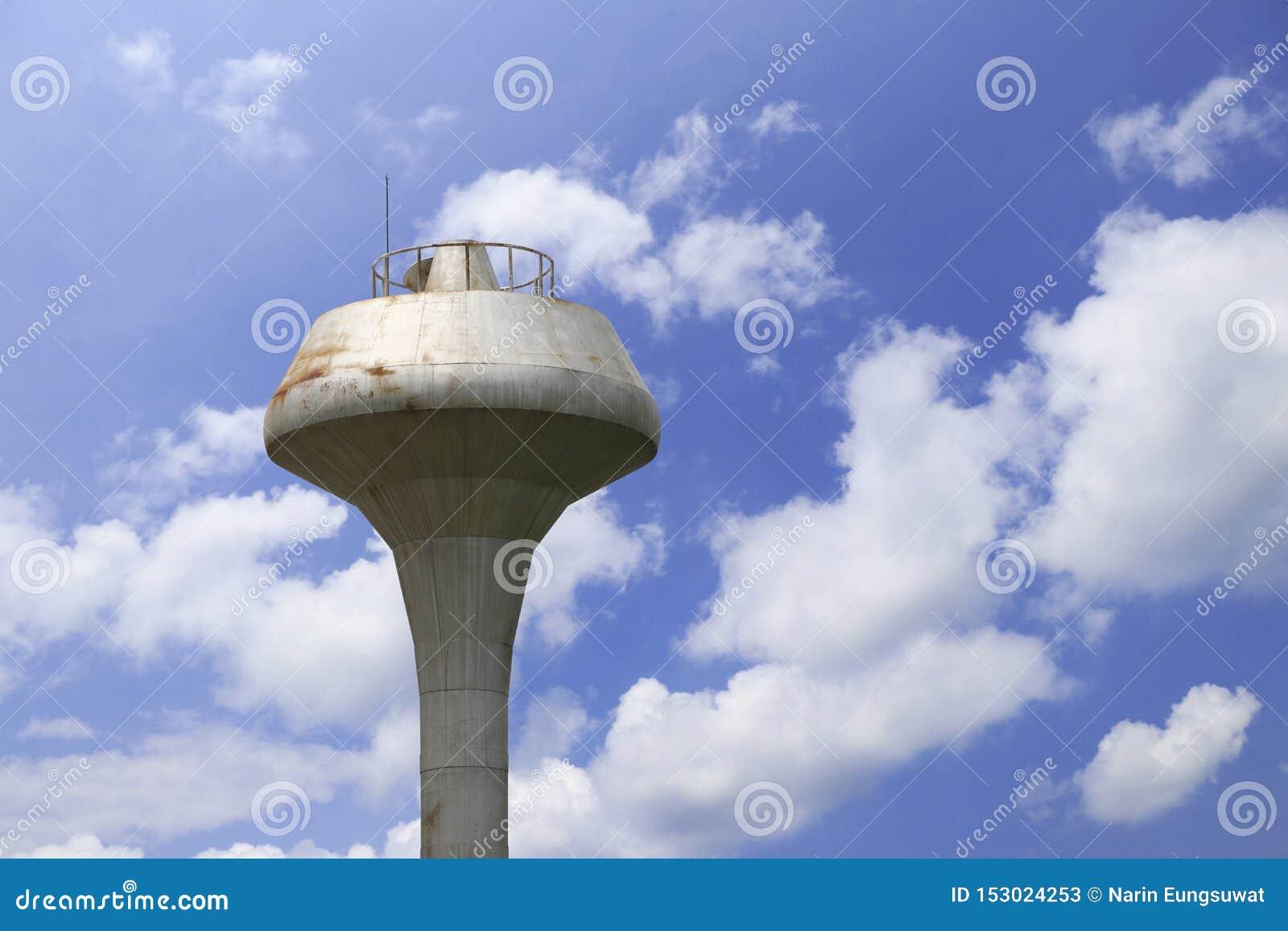 Vattentorn med moln och bakgrund för blå himmel