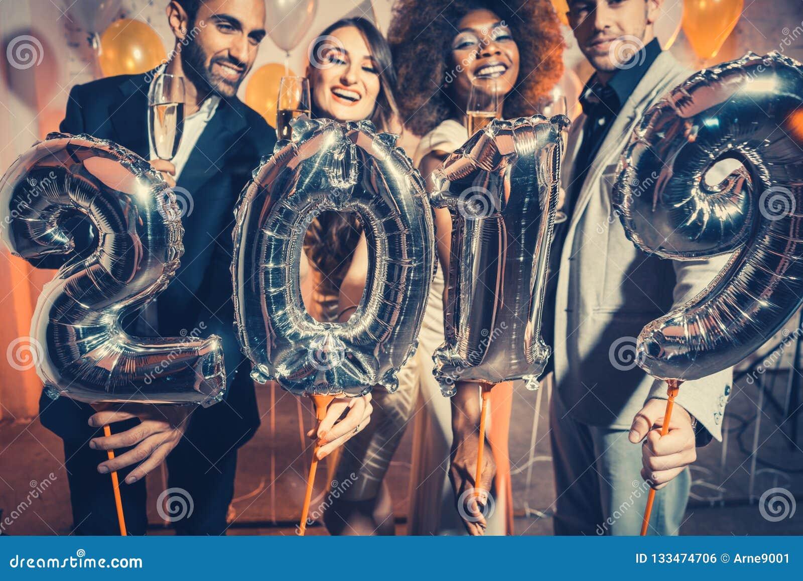 Vaya de fiesta las mujeres y a los hombres de la gente que celebran la Noche Vieja 2019