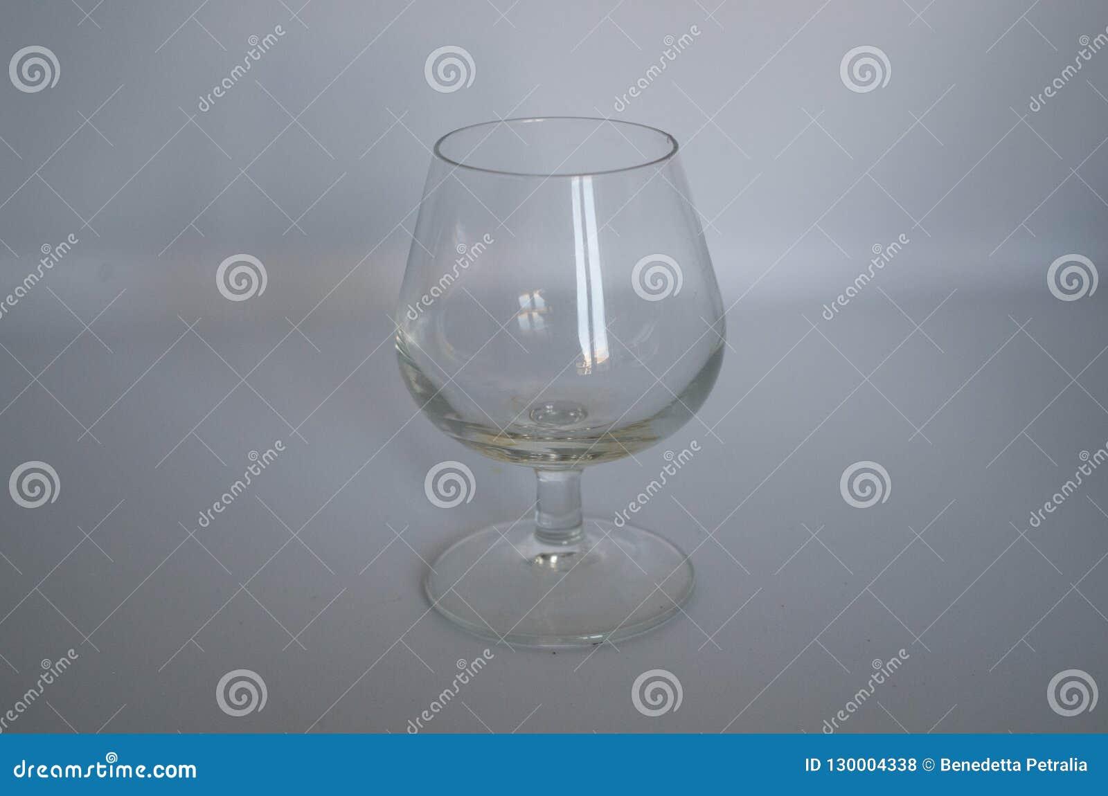 Vazio de vidro do conhaque no fundo branco