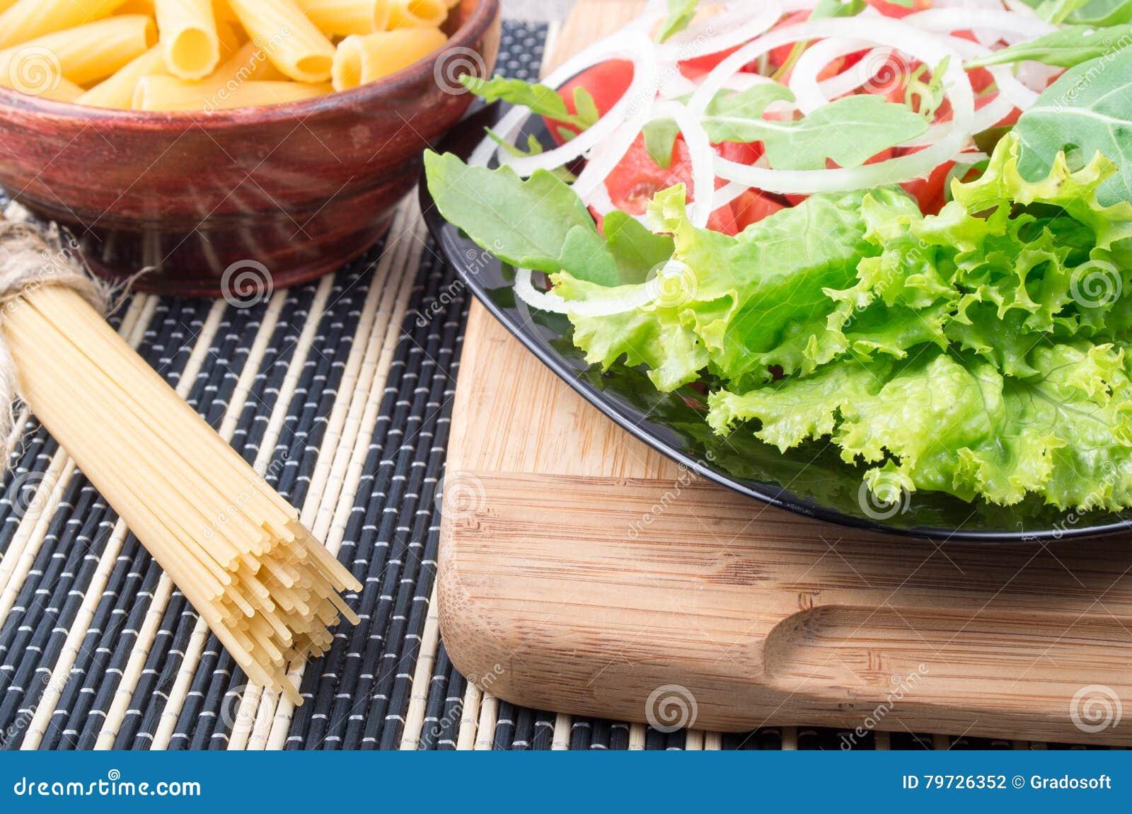 Vea el primer en una placa negra con la ensalada fresca en un stan de madera