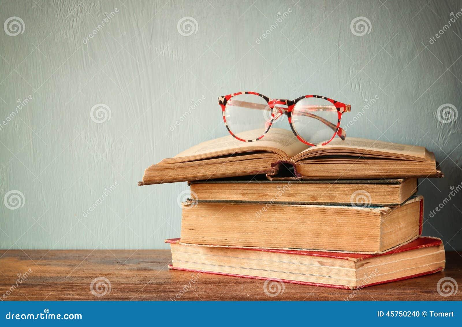 Vecchi libri con i vetri d annata su una tavola di legno retro immagine filtrata