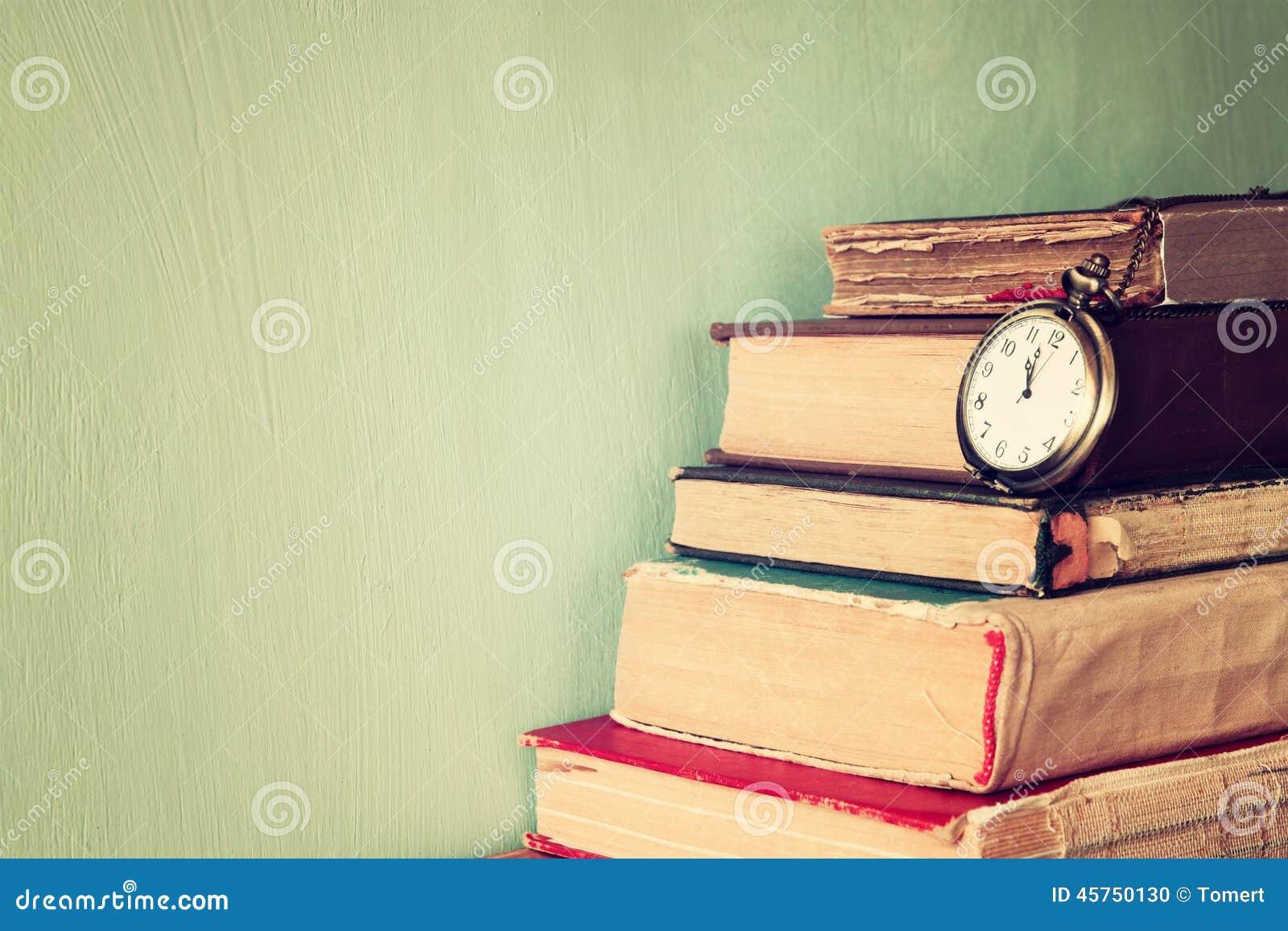 Vecchi libri con l orologio da tasca d annata su una tavola di legno retro immagine filtrata