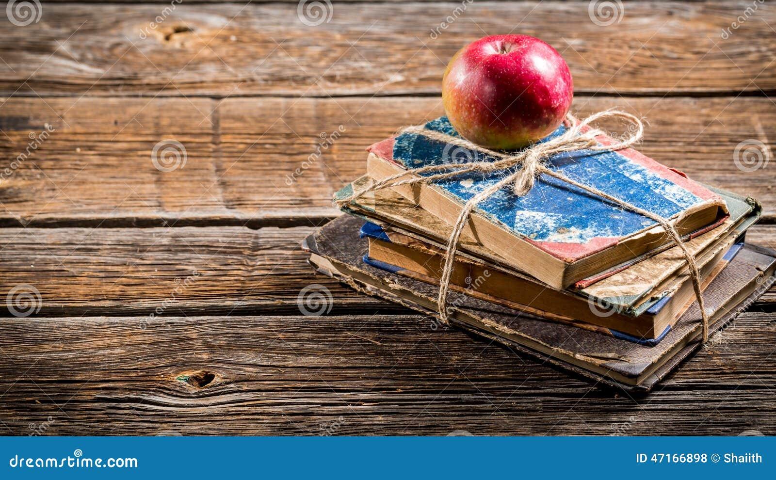 Vecchi libri e mela sullo scrittorio della scuola