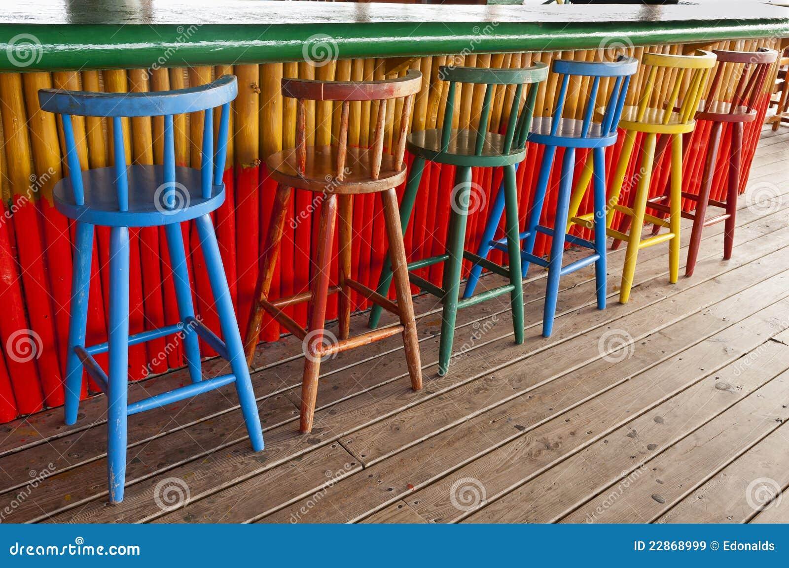 Vecchi sgabelli di barra ad un pub tropicale immagine stock