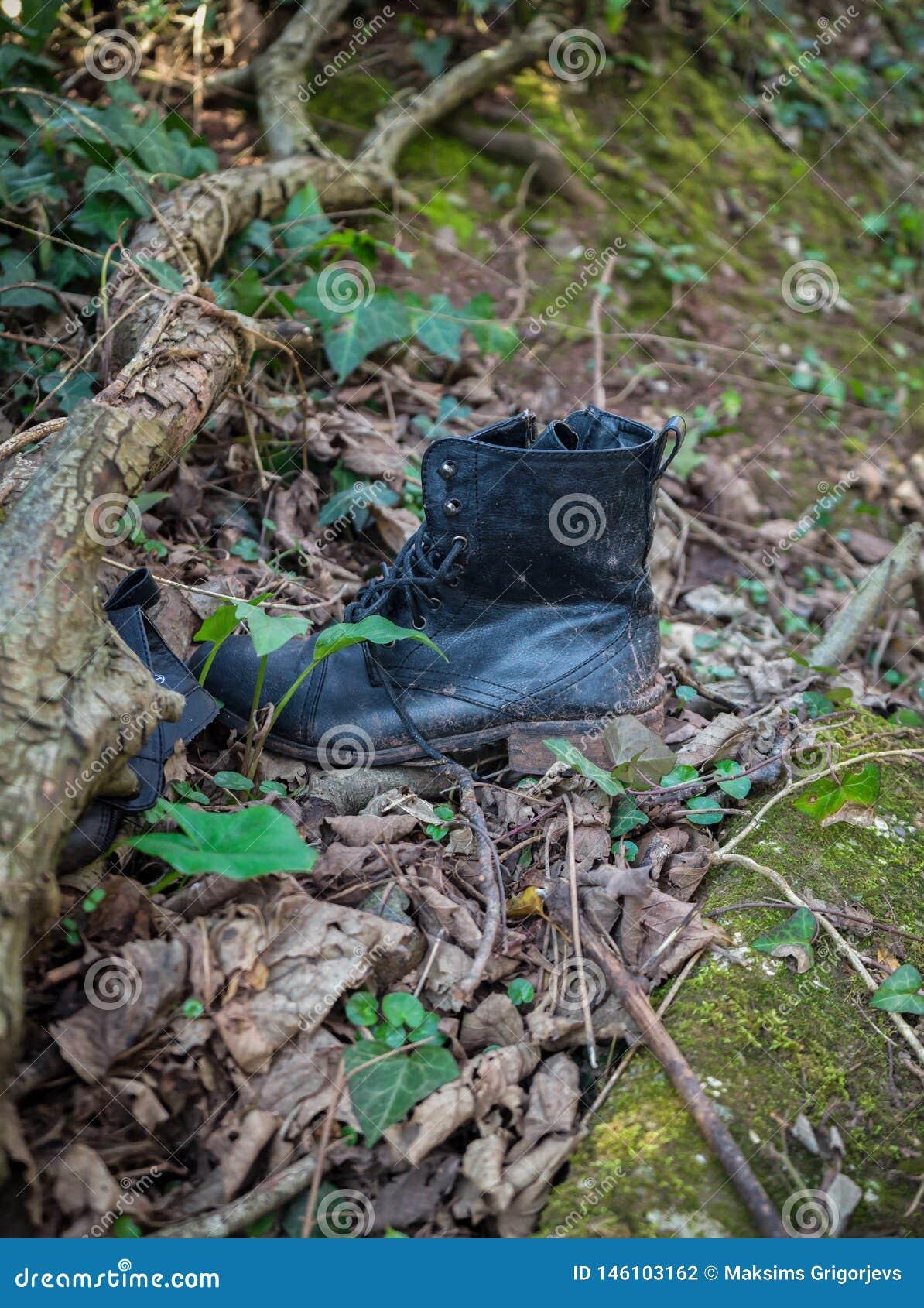 Vecchi stivali sporchi neri di cuoio miseri lasciati in legno