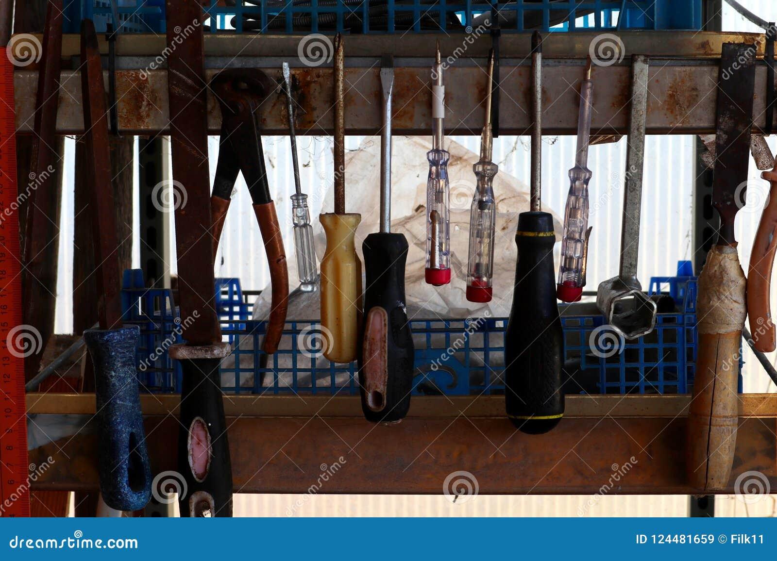 Vecchi strumenti che appendono su uno scaffale del ` s del lavoratore Cacciaviti, martello e pinze