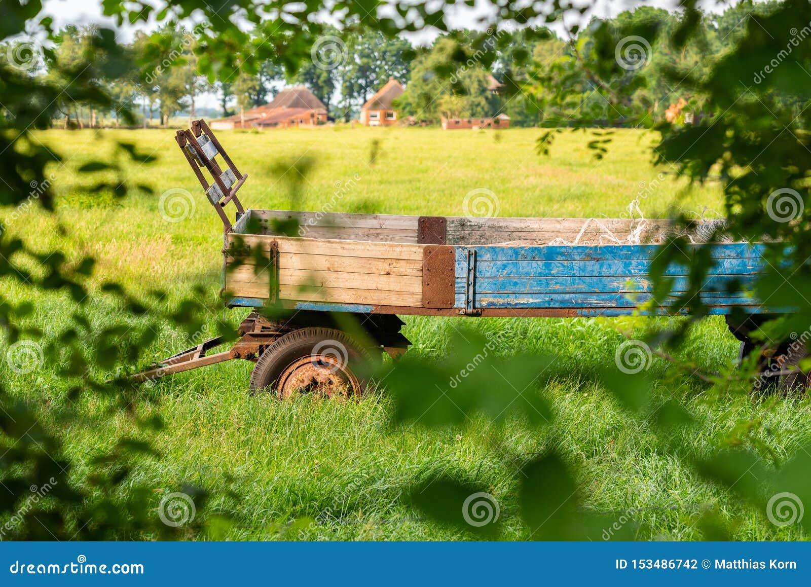 Vecchi supporti del rimorchio dell azienda agricola abbandonati su un campo