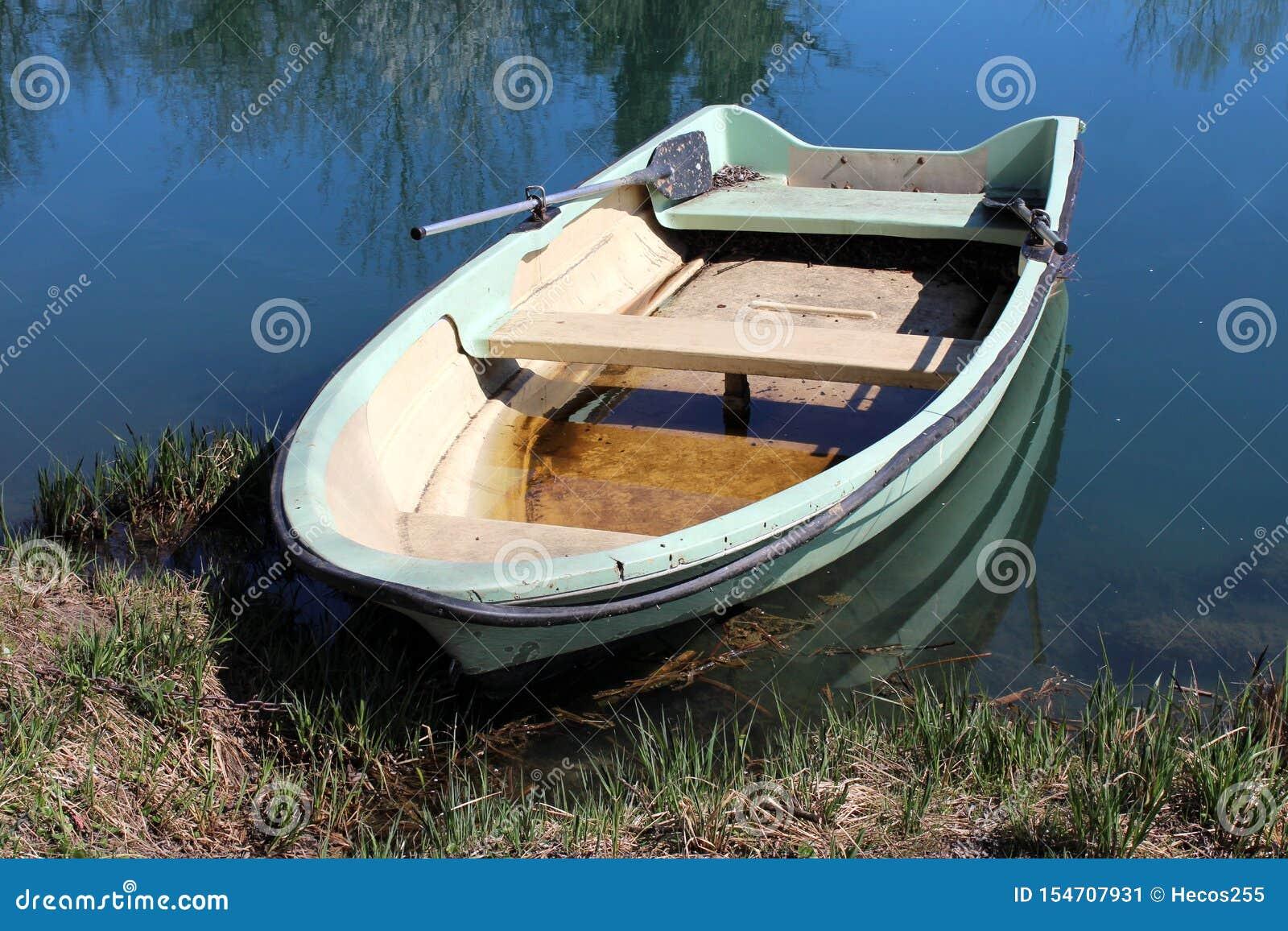 Vecchia barca di fiume verde chiaro dilapidata della vetroresina legata alla sponda del fiume circondata con erba non tagliata ed