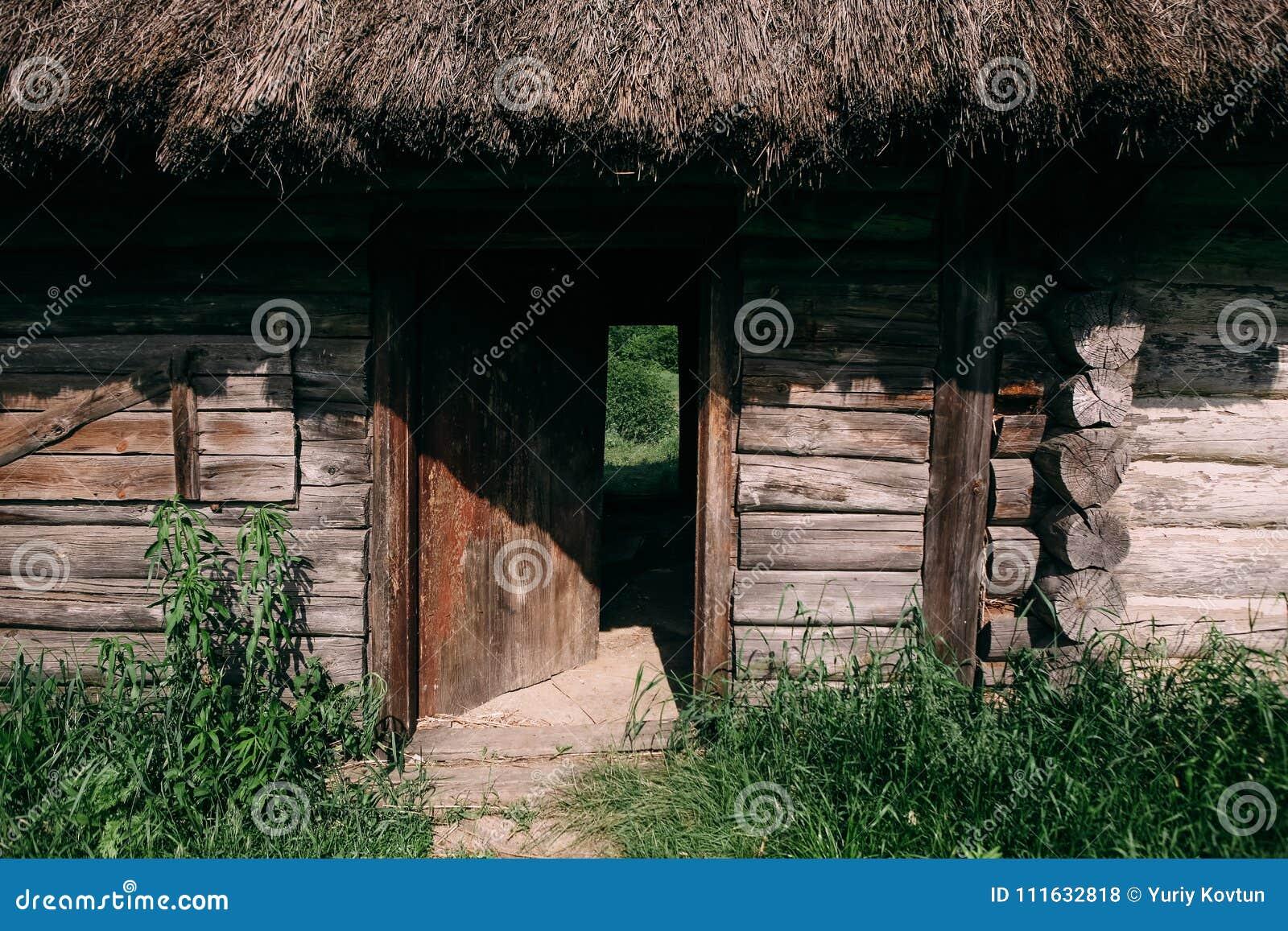 Vecchia casa di legno misera con un tetto rotto vicino