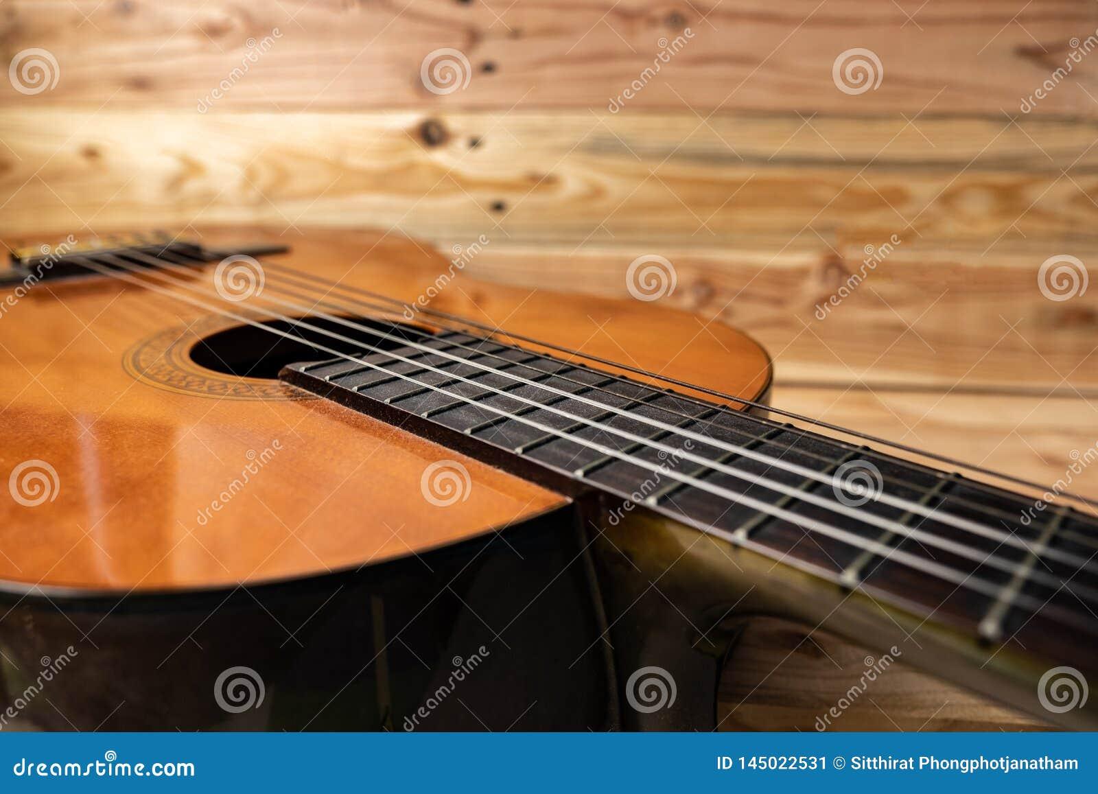 Vecchia chitarra classica su fondo di legno