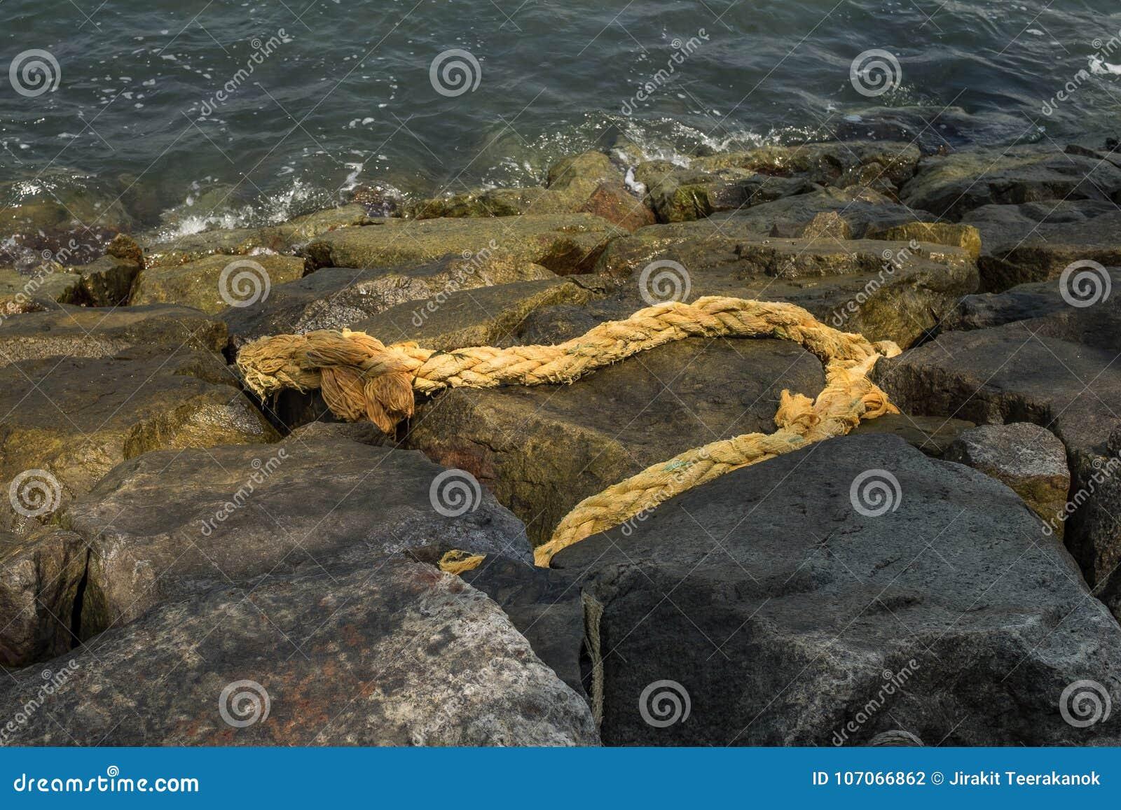 Vecchia corda marcia della canapa sulla riva rocciosa