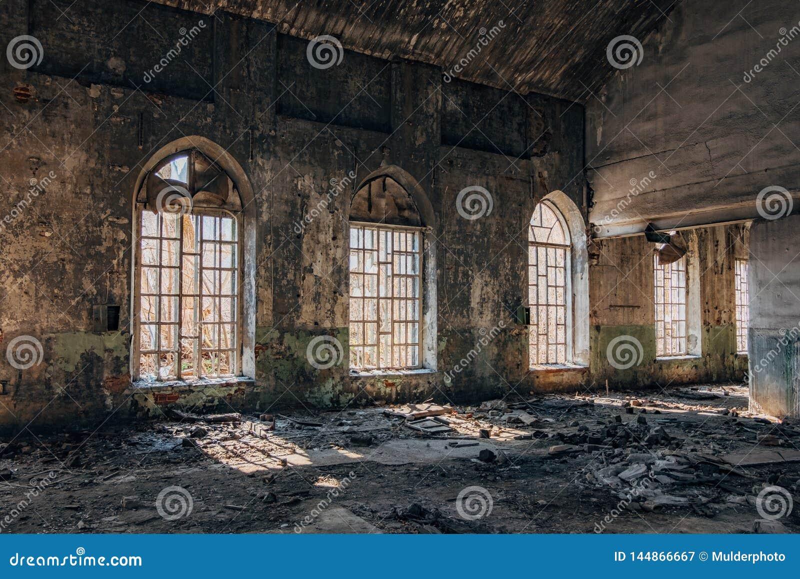 Vecchia costruzione abbandonata con le finestre di lancetta rotte dentro
