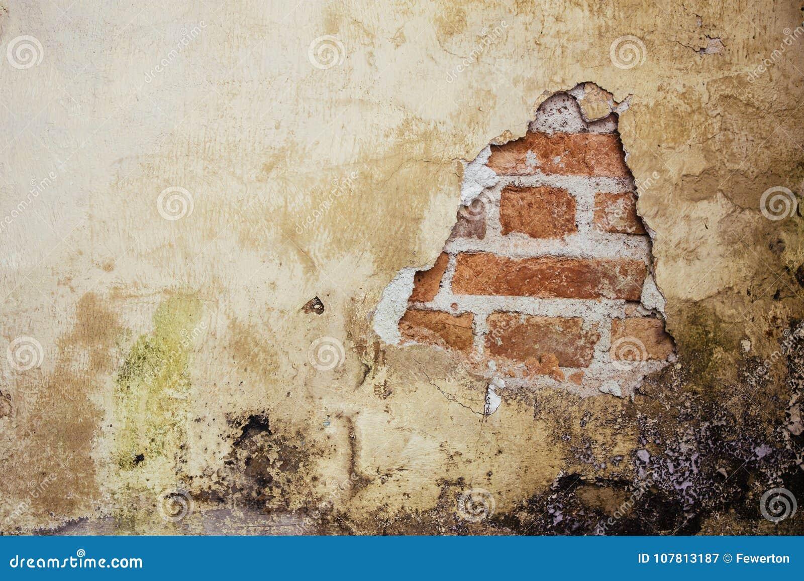 Vecchia facciata intonacata sporca e grungy della parete di una casa abbandonata con un foro che mostra i mattoni rossi di fondo