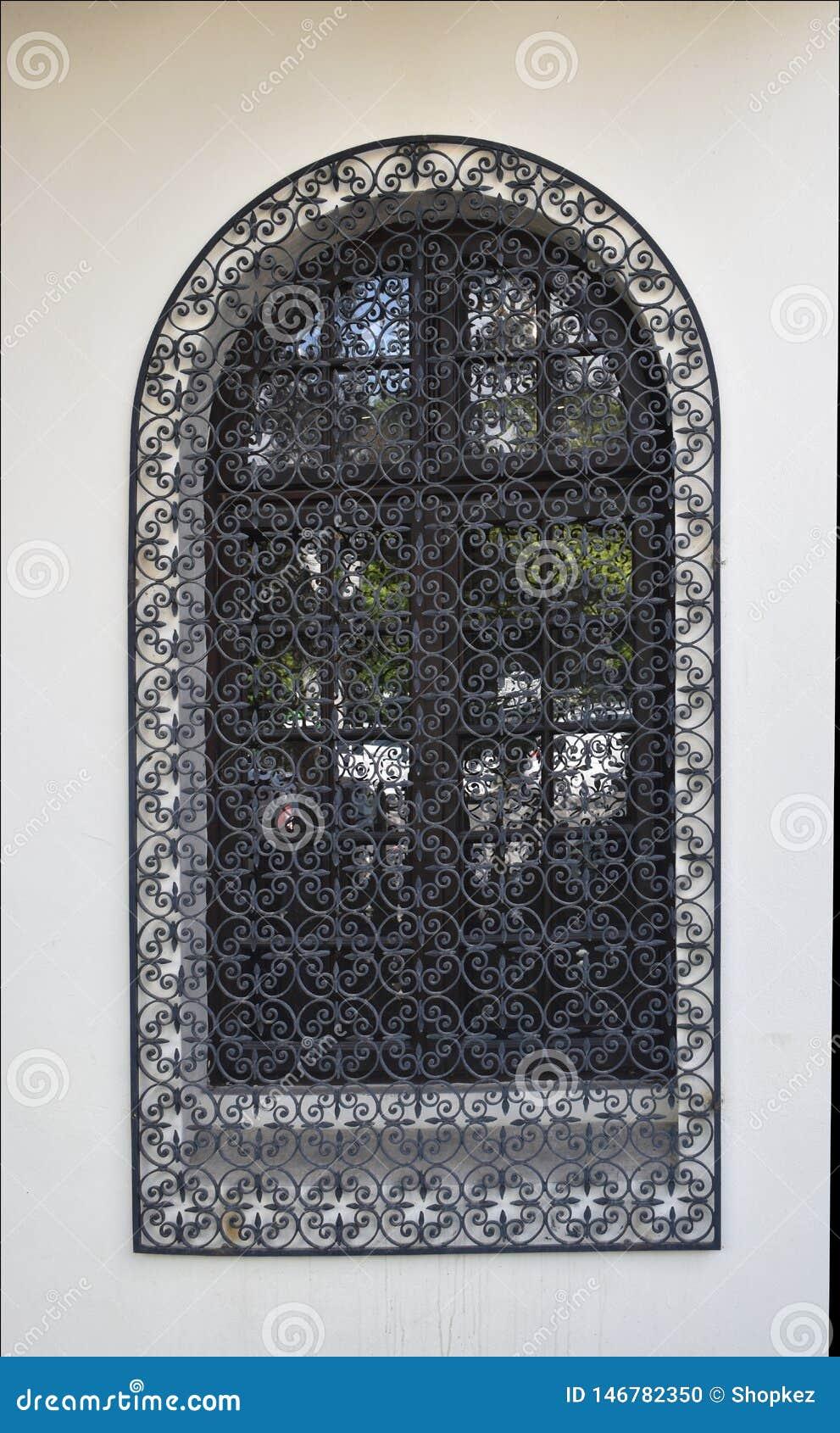 Vecchia finestra veneziana con la griglia nera del ferro