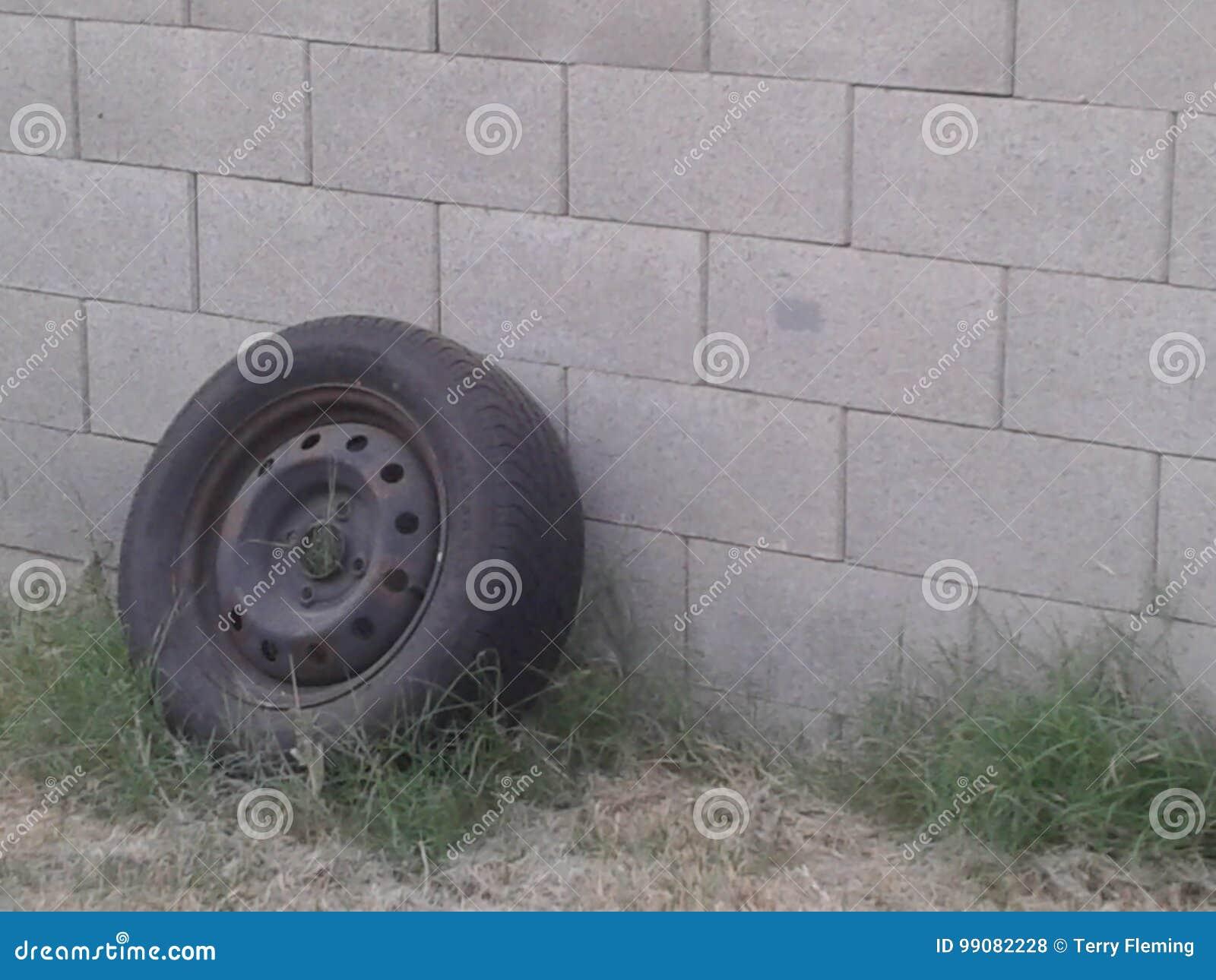 Vecchia gomma che pende su contro un muro di mattoni grigio