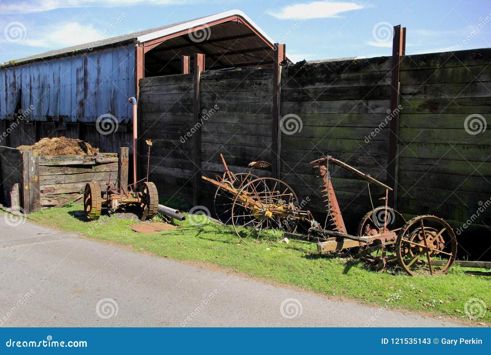 Vecchia menzogne arrugginita d annata dell attrezzatura dell azienda agricola inutilizzata su un bordo di erba i