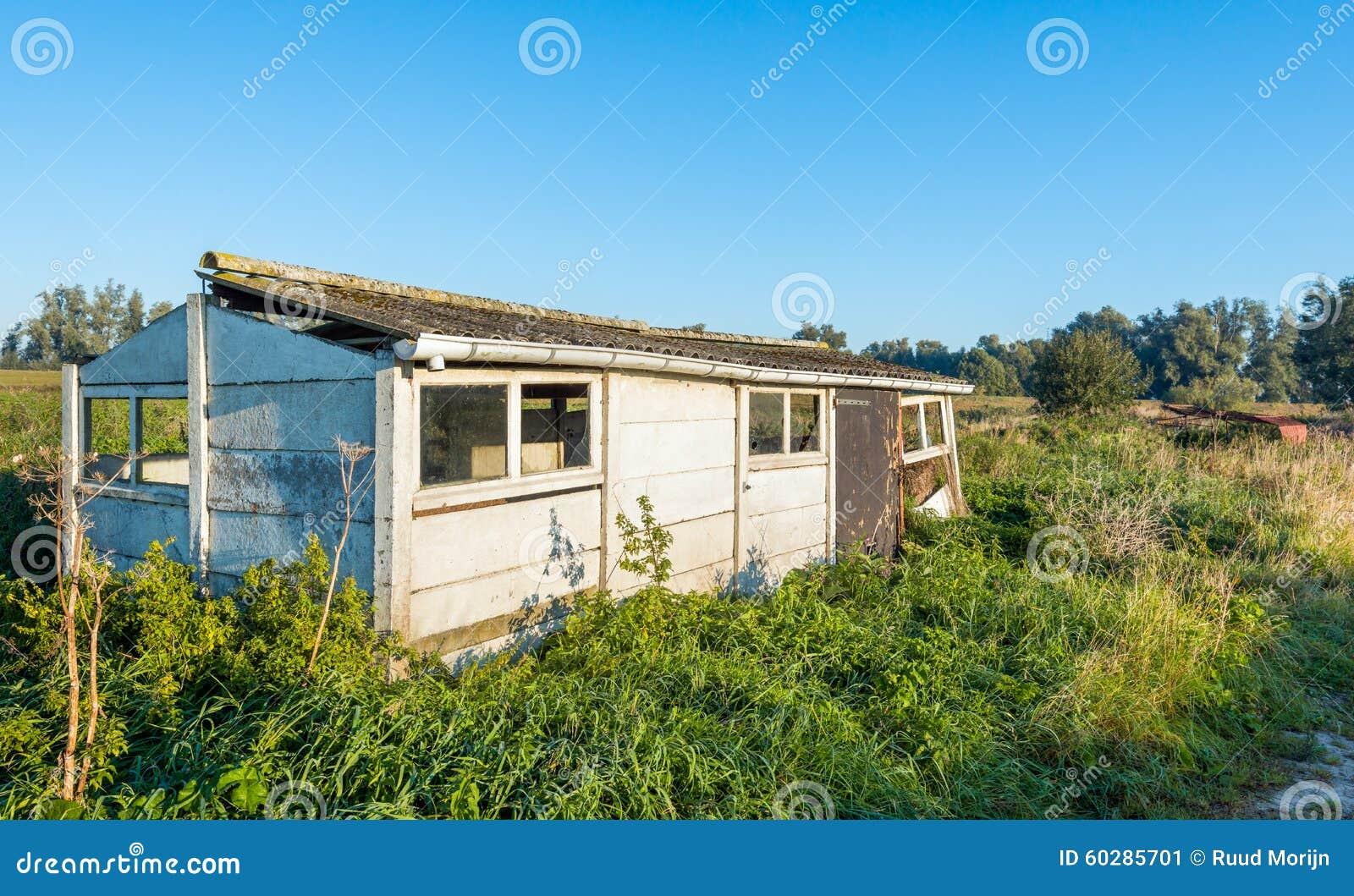 vecchia piccola tettoia dilapidata fatta delle lastre di cemento armato e con un tetto ondulato alla luce solare di primo mattino nella stagione di caduta
