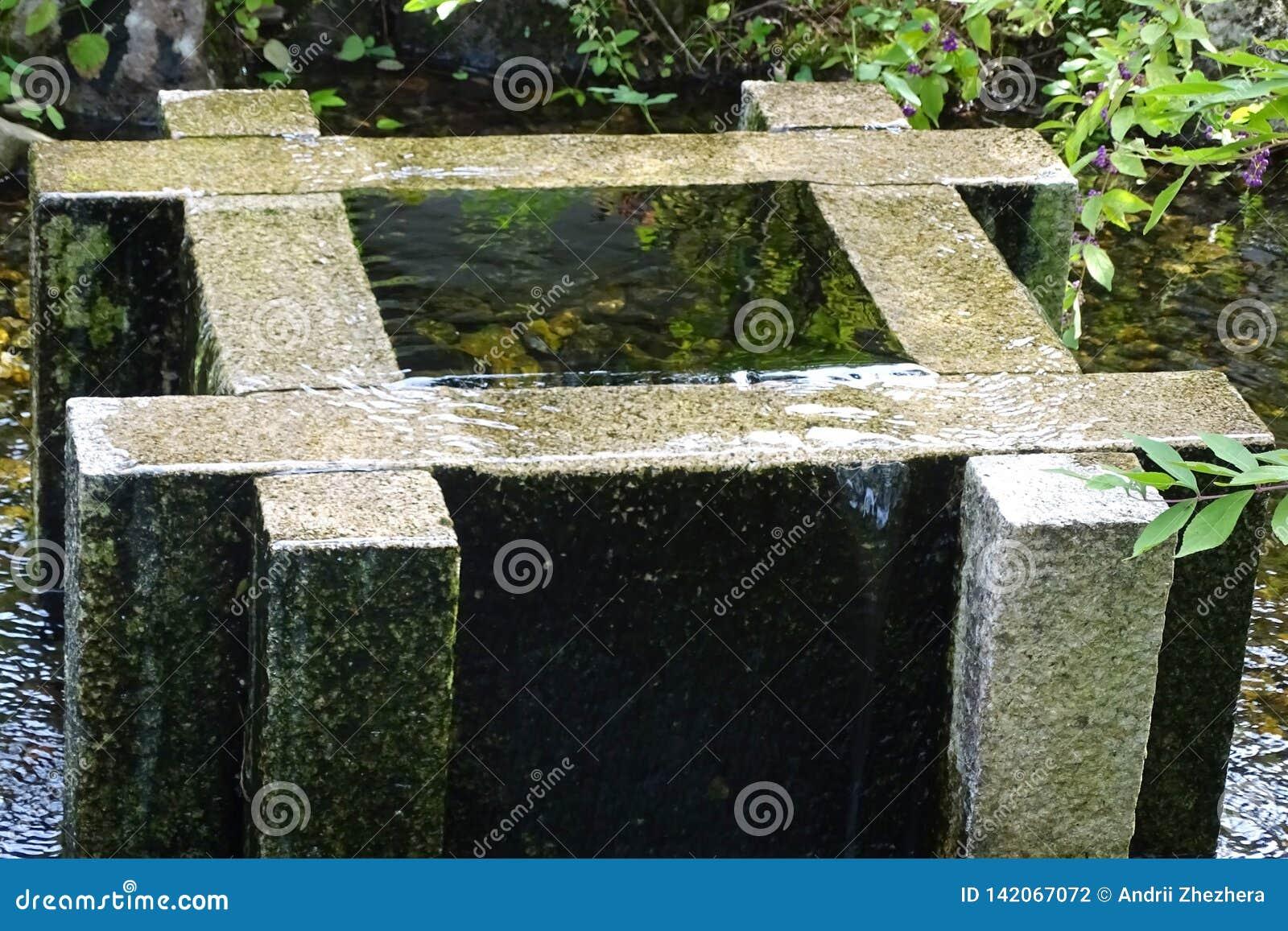 Vecchia pietra bene piena di acqua in un parco