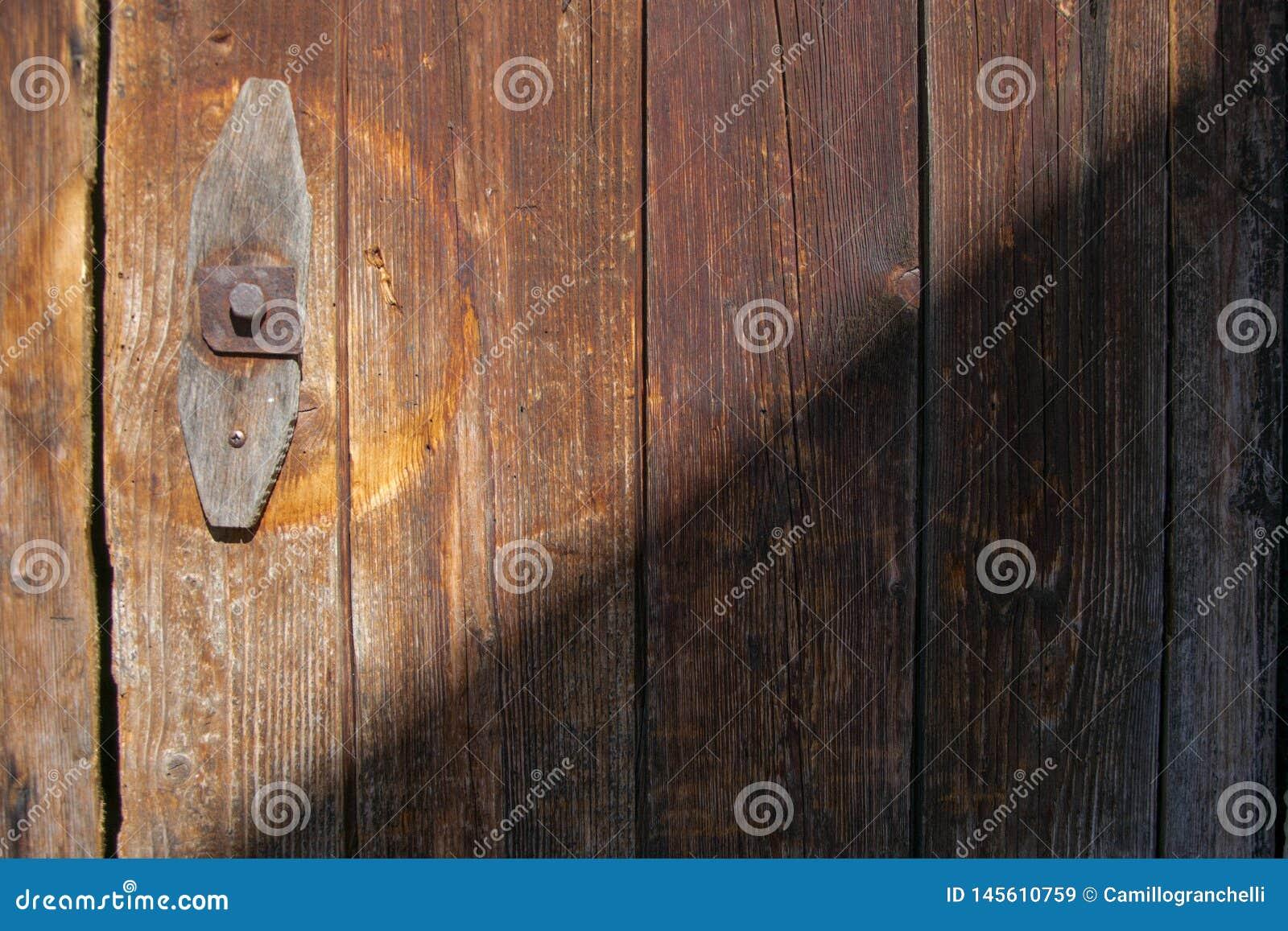 Vecchia porta con le plance di legno alla luce e ad ombra