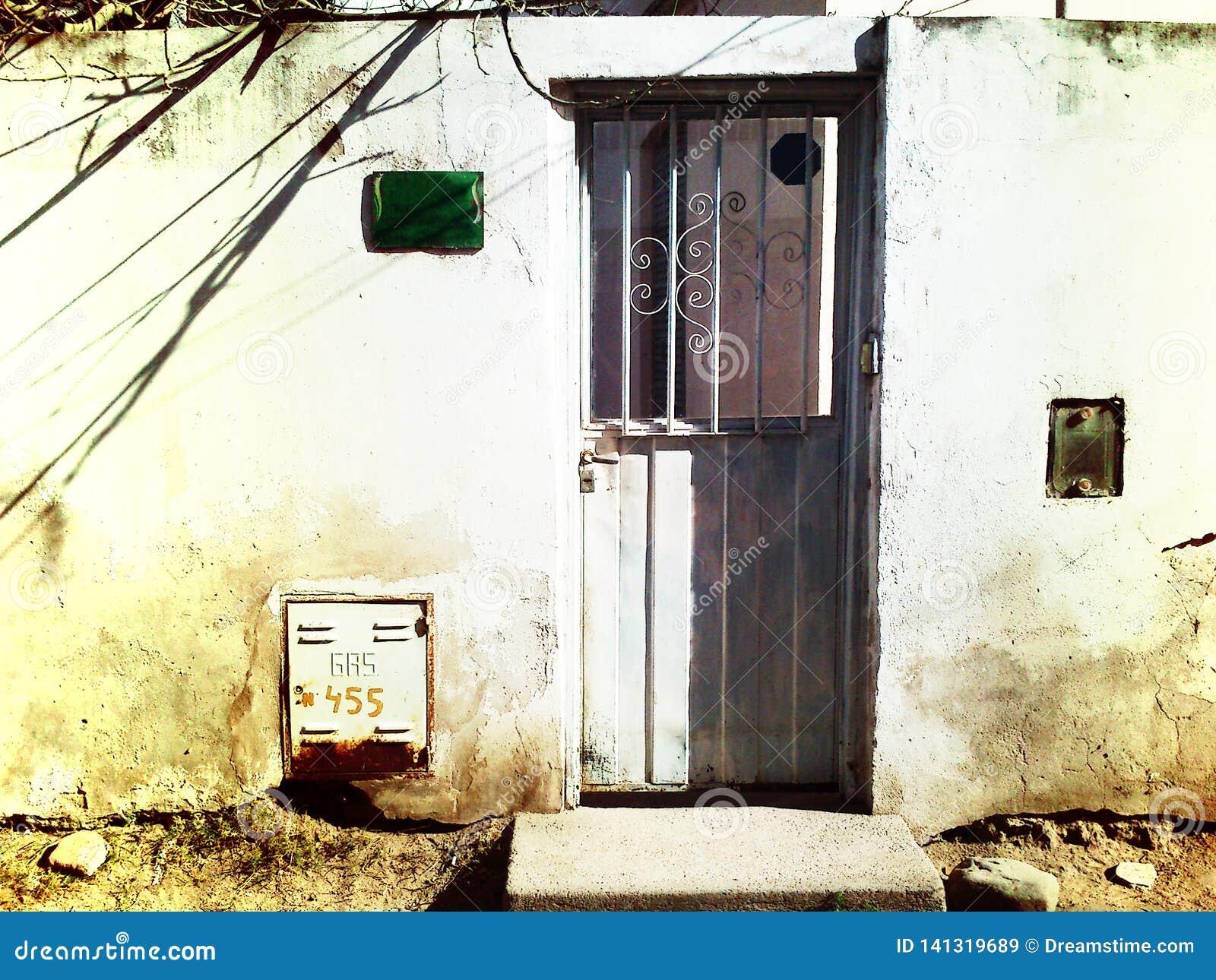 Vecchia porta grigia della lamiera sottile in una parete consumata