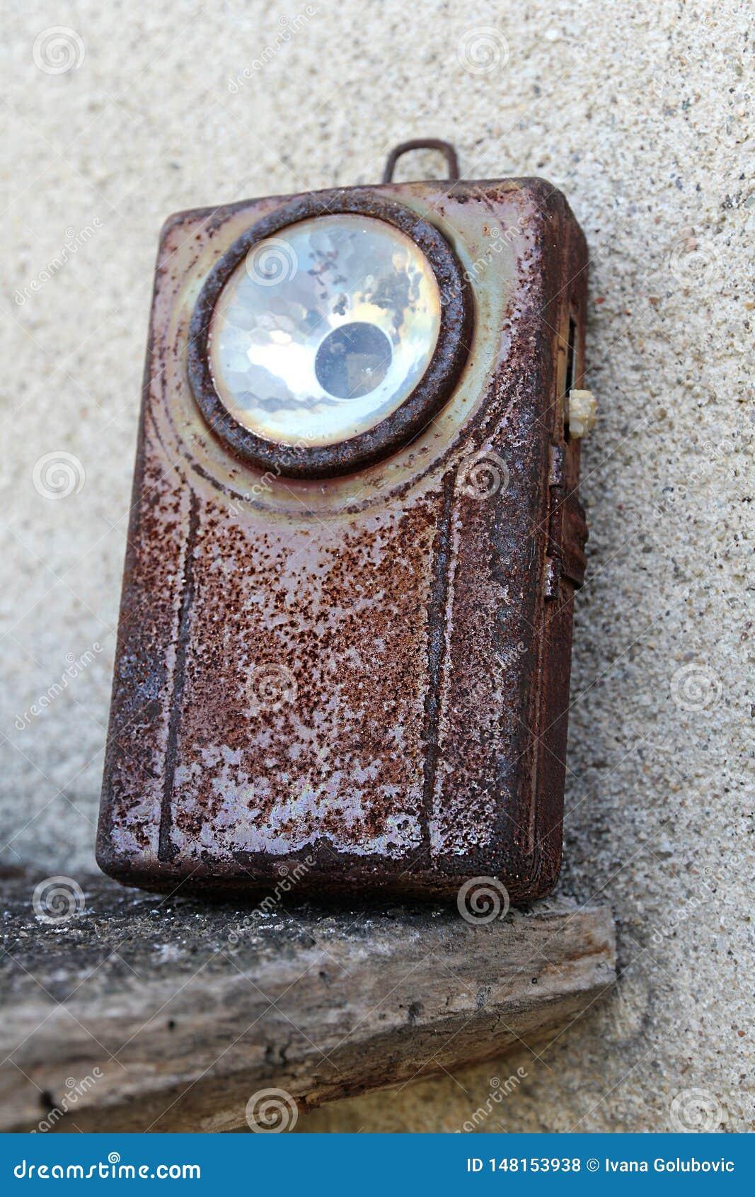 Vecchia, torcia elettrica militare arrugginita della tasca con il commutatore conservato