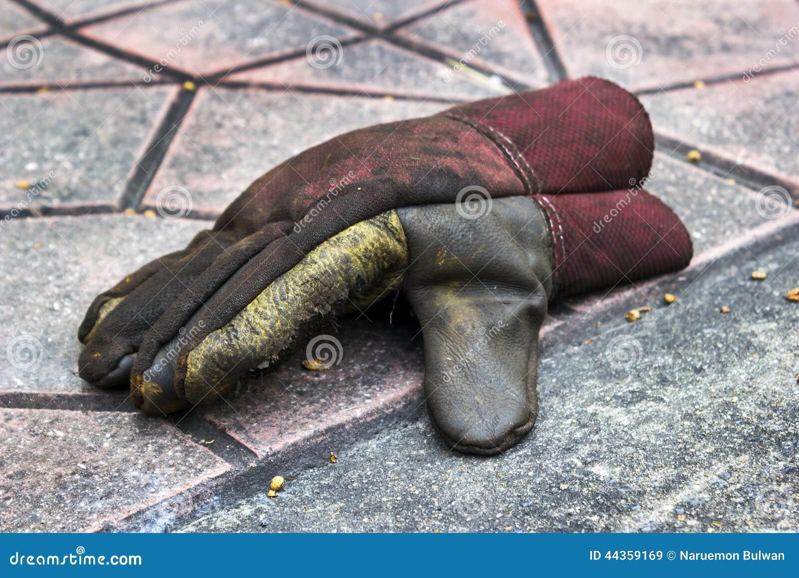 Vecchio guanto lacerato su terra
