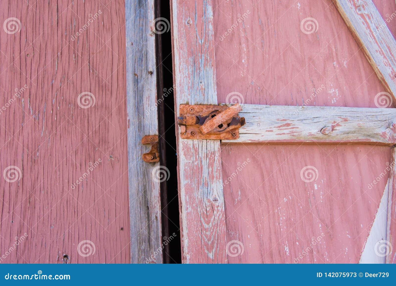 Vecchio ha sbiadito la porta di granaio rossa che è dipinta